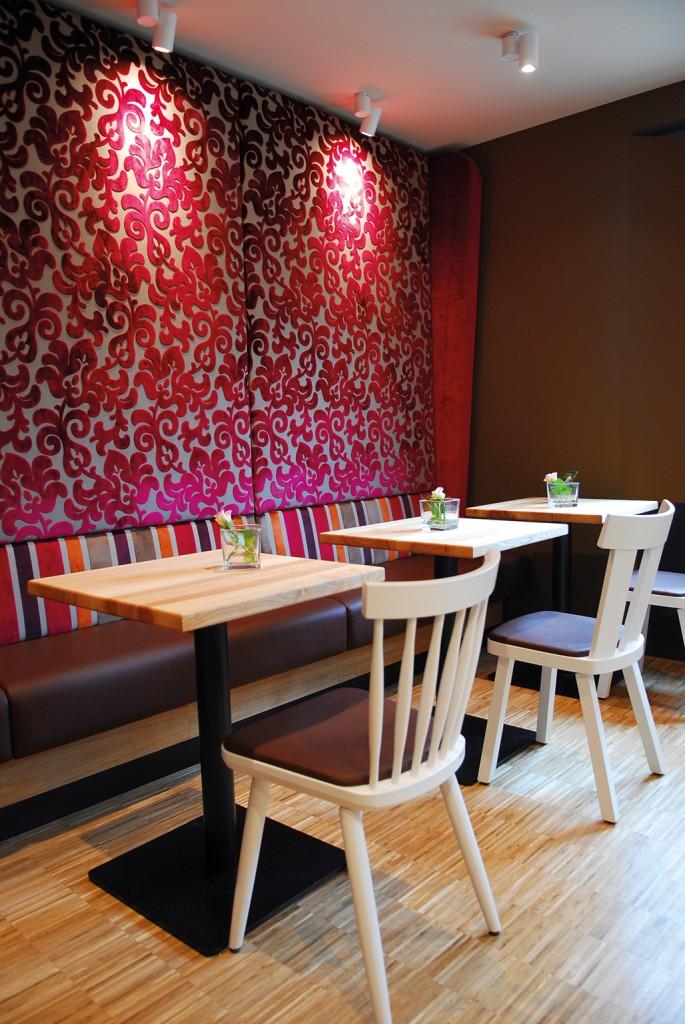 Wohnliche Bäckerei-Cafés: Eine bis zur Decke hochgezogene Ohrenbank ist nicht nur ein optischer Hingucker, sondern sorgt auch für eine gute Akustik. Die Stühle Mika und Paul bilden mit ihrer leichten Optik eine ideale Ergänzung.