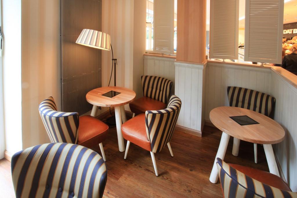 """Wohnliche´Bäckerei-Cafés: In Retro-Optik ist der Lounge-Bereich mit Sesseln """"Fritz"""" und passenden kleinen Holztischchen (Modell 30033), die Ausfräsungen für iPads enthalten, eingerichtet."""