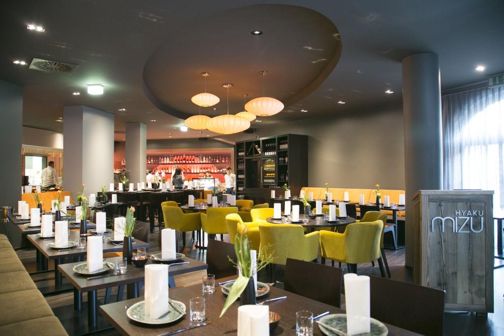 """Im Znetrum des Restaurants steht ein runder Tisch mit den Stühlen """"Marie"""". Restaurant Möblierung"""