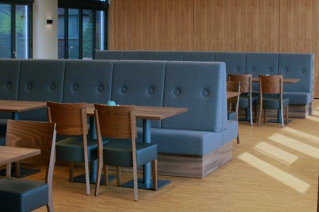 """Mitarbeiterkantine Bänke mit überdimensionaler Knopfheftung zonieren den Raum, dazu gesellen sich die Stühle """"Milia"""" mit Lederpolstern. Holztöne schaffen Behaglichkeit."""